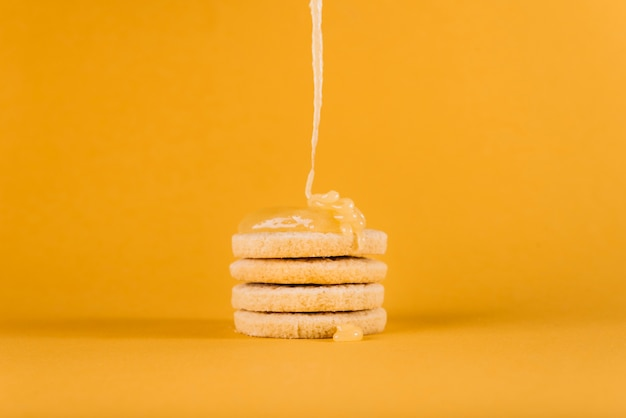 Lemon curd dripping on stacked cookies on yellow surface