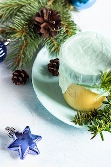 Lemon curd in glass jar. fir branches, cones and christmas decorations.