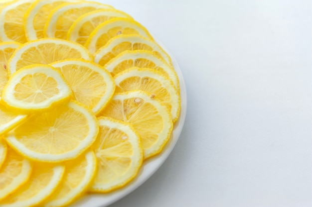 Lemon cut into slices on a white plate on white background.