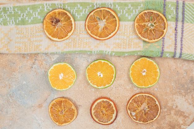 Limone e fette d'arancia essiccate sulla superficie in marmo.