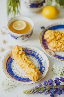Лимонные эклеры и чай с лимоном в старинном чайном сервизе и цветы на белом
