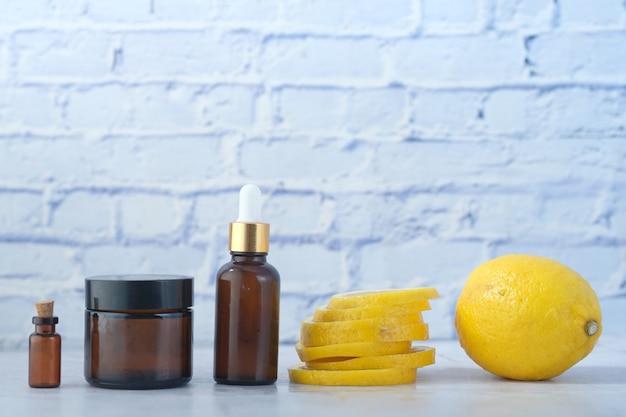 Эфирное масло лимона и ломтик лимонного стола с копией пространства