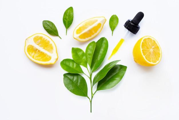 Lemon essential oil and lemon fruits on white