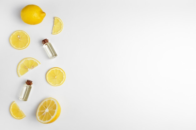 Lemon essential oil. lemon slices on white background.