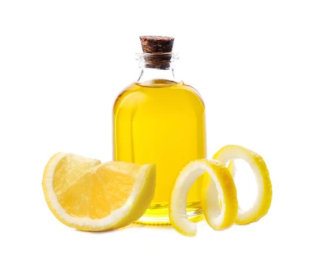 Эфирное масло лимона с ломтиком лимона на белом фоне. полезный масляный ингредиент.