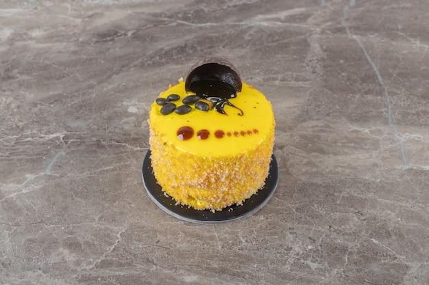 Copertura al gusto di limone su una piccola torta su superficie di marmo