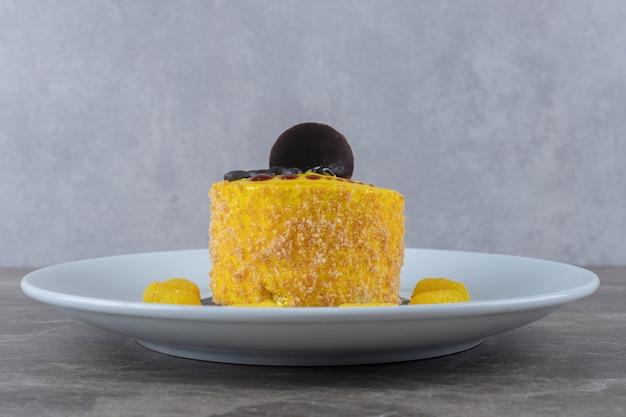 Rivestimento aromatizzato al limone su una piccola torta su un piatto da portata su superficie di marmo