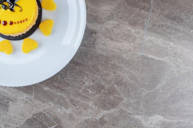 Rivestimento al gusto di limone su una piccola torta circondata da caramelle gommose su un piatto su una superficie di marmo