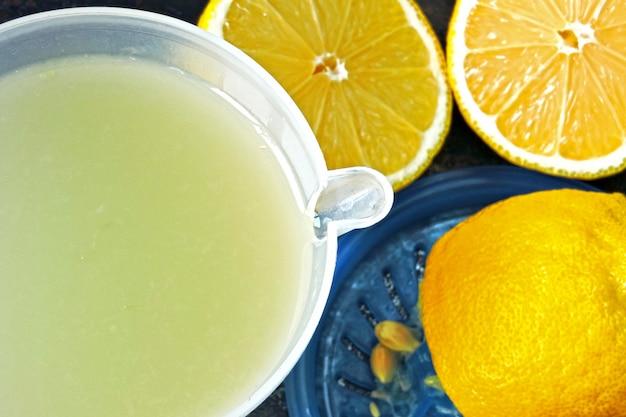 Лимонный фреш и лимоны. соковыжималка для цитрусовых. концепция похудения с лимонным соком.