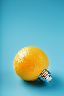 Lemon fruit as a light bulb on blue