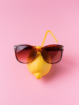 Lemon fruit in sunglasses on pink background, vacation concept