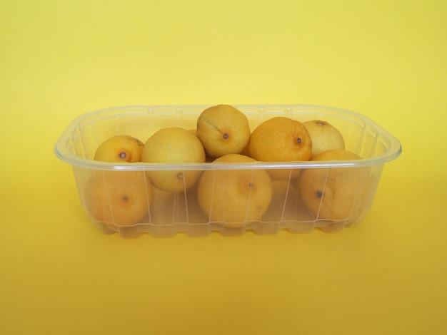 黄色の背景の上のプラスチックの箱にレモンの果実