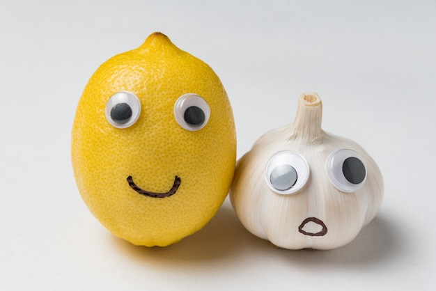 Lemon and garlic with funny faces and googly eyes on white background. health products