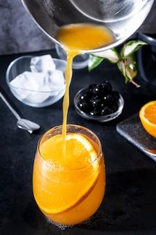 Комбуча с лимоном и имбирем в стакане с долькой апельсина