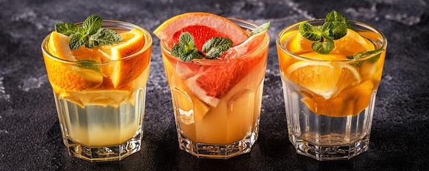 Лимон, грейпфрут, апельсиновый домашний коктейль / вода, насыщенная фруктами детоксикации, выборочный фокус.