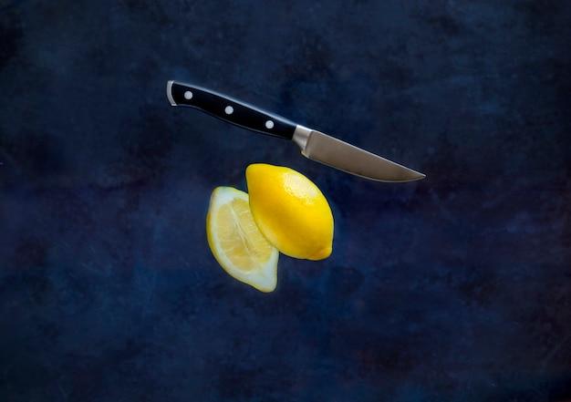 暗い背景にフルーツナイフで切るレモンの半分。食品の浮揚