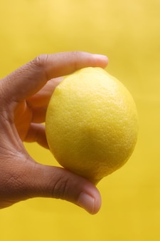 Lemon in hand on with yellow background