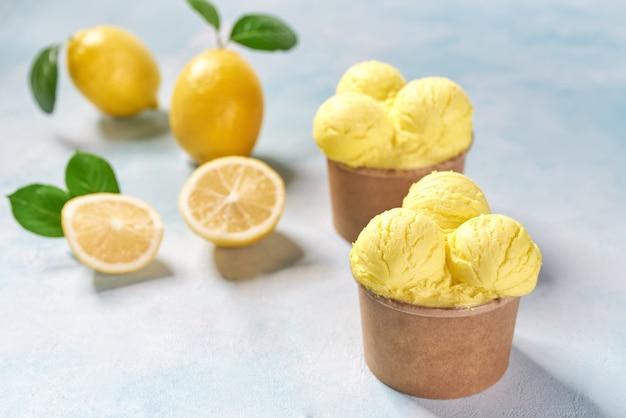 レモンアイスクリームとミント色の背景、トップビューで紙コップに新鮮なレモン