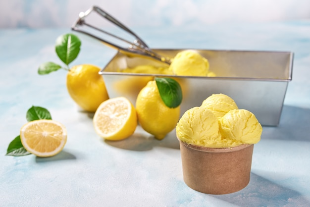 レモンアイスクリームとミント色の背景上の紙コップで新鮮なレモン