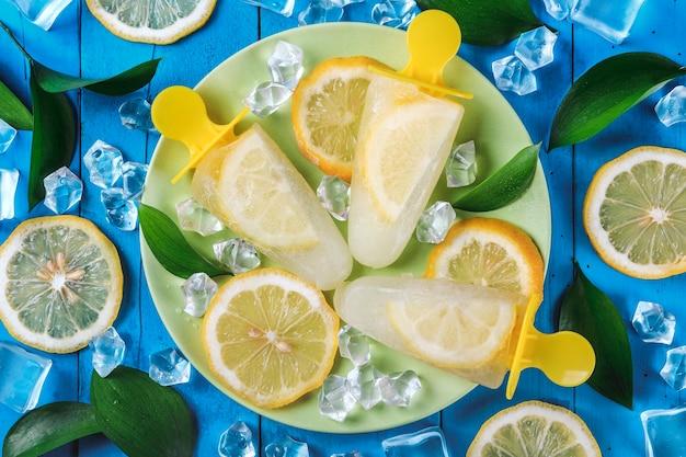 Лимонное мороженое на палочке на синем деревянном столе с кубиками льда