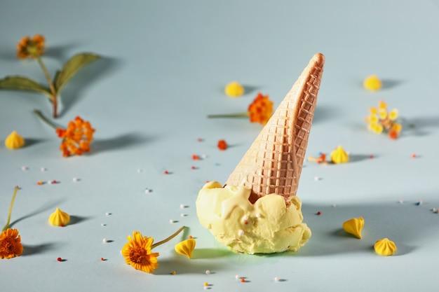 Лимонное мороженое с вафельным рожком на синем фоне с желтыми цветами.