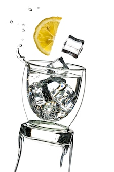 Lemon and ice cubes fall into a splashing cocktail.