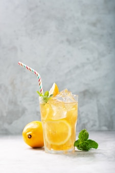 Lemon ice tea on concrete gray background with mint and ice