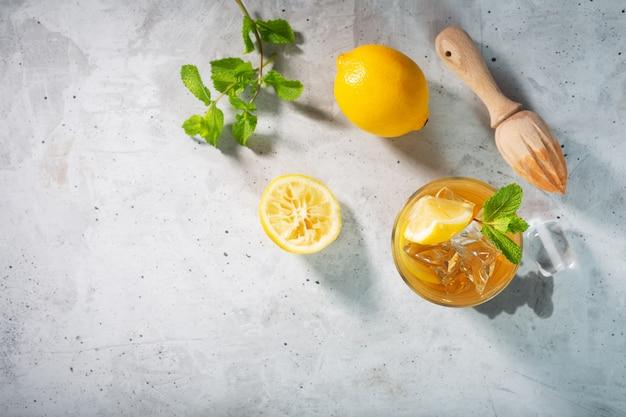 Лимонный ледяной чай на бетонном сером фоне с мятой и льдом
