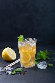 Холодный чай с лимоном на темном фоне с мятой и льдом, ещз мшуц