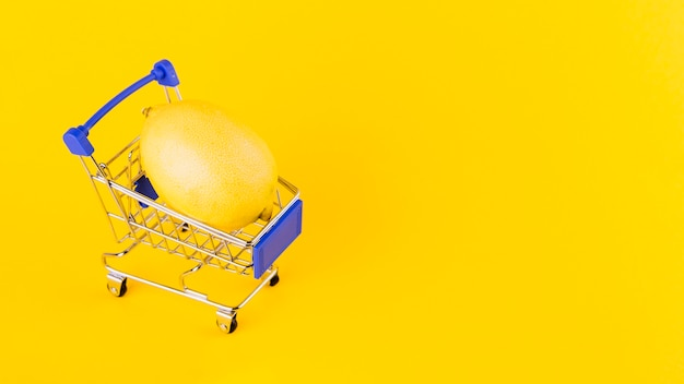 Lemon inside the shopping cart against yellow background