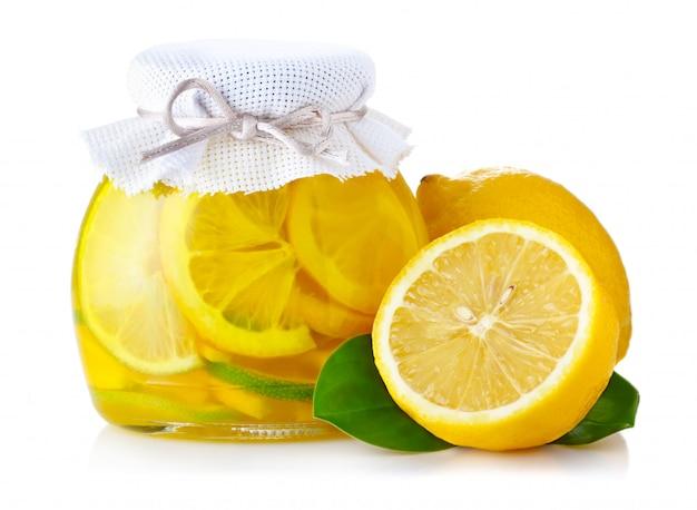 Lemon jam with ripe fruits isolated on white