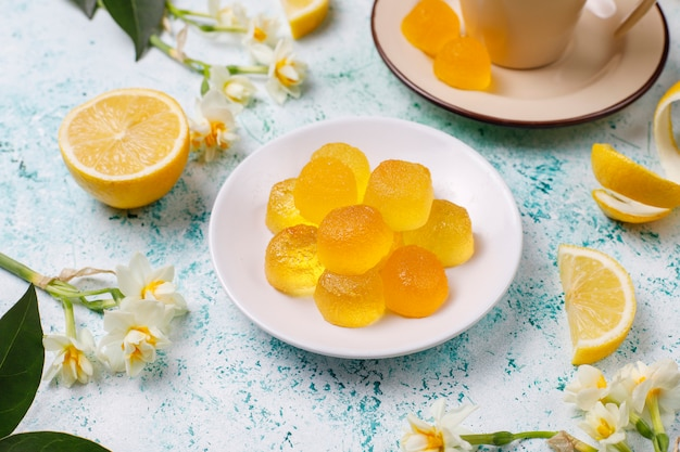 Lemon jelly candies with fresh lemons ,top view