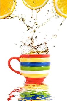 反射のあるカラーカップにレモンジュースとお茶のスプラッシュ