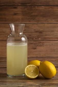 Succo di limone nel contenitore di vetro con frutta sul tavolo di legno