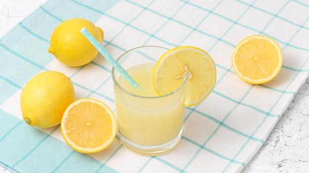 背景に青いストローと新鮮なレモンとグラスのレモンジュース