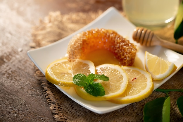 Lemon juice with honey on wooden table,  lemons and sage leaves.