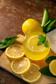 Lemon juice with honey on wooden table,  lemons and sage leaves