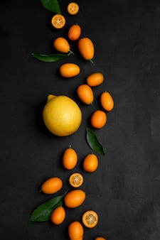 Lemon and kumquats decorated with leaves on black surface