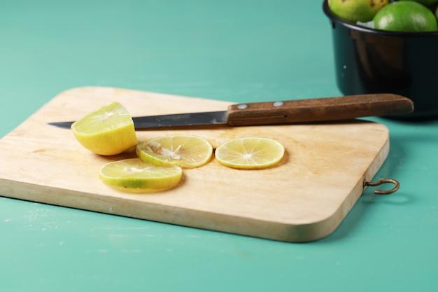 나무에 부엌 칼으로 레몬 라임 슬라이스 음식과 신선한 음료 레몬 육즙 수 제 요리 정육점.
