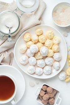 Лимонные безе и белые на фоне чая, сахара на белом фоне. вид сверху, вертикальный.