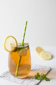 Lemon and mint herbal tea glass with green drinking straw on folded tablecloth against white backdrop