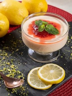Лимонный мусс в хрустальной миске с клубничным желе и мятой.