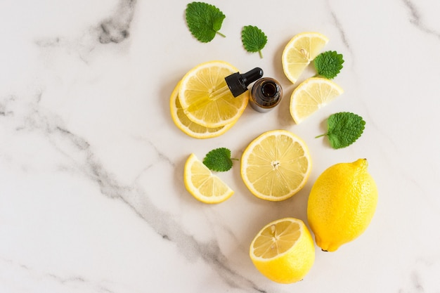 Лимонное масло в бутылке с ппеткой с зелеными листьями мелиссы и дольками лимона на белом мраморном фоне. вид сверху. увлажняющий, антистрессовый эффект.