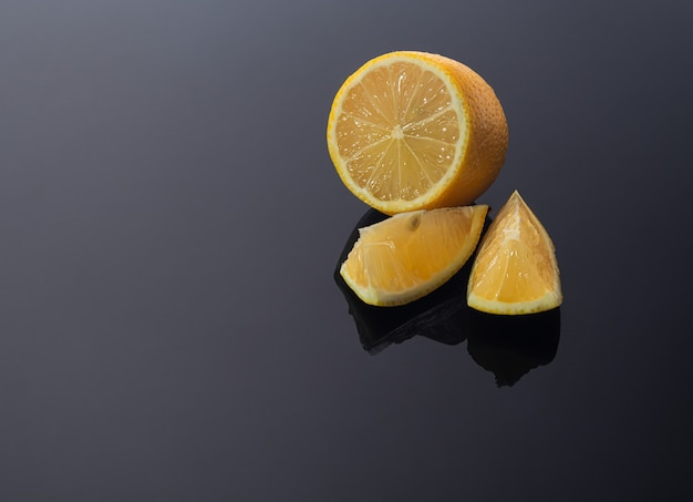 暗い光沢のある表面にレモンがあり、影が固い。ビタミンと健康の概念。