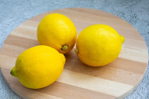 明るい木のまな板と灰色のテーブルの上のレモン。