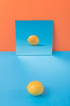 オレンジに分離された青いテーブル上のレモン