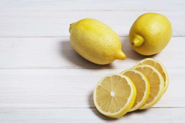 Лимон на белой деревянной предпосылке. дольки лимона. скопируйте пространство. элементы дизайна.