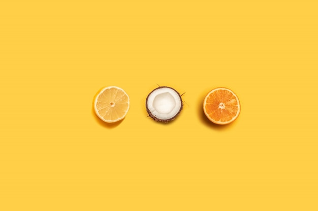 Lemon, orange and coconut on a yellow background.