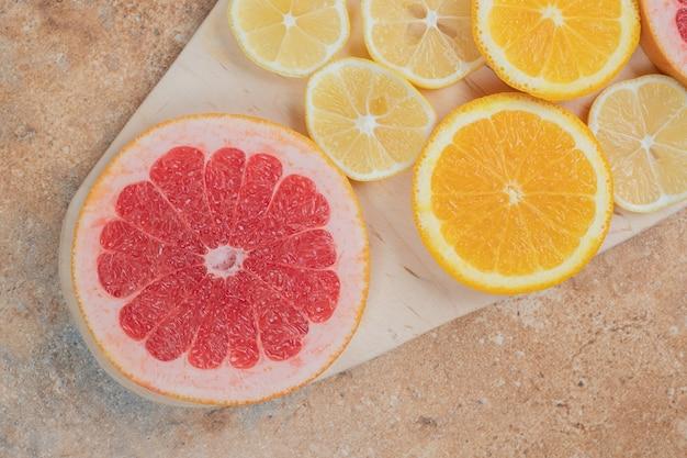 Fette di limone, arancia e pompelmo su tavola di legno.