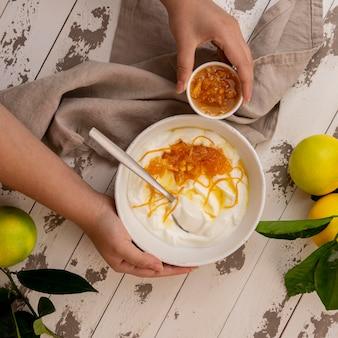 나무 테이블에 요구르트와 꿀 레몬 껍질